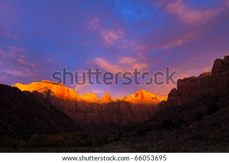 The sun kisses the top of the Towers of the Virgin at Zion Canyon National Park, Utah. - stock photo