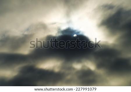 The sun looks through through a gleam in the cloudy sky - stock photo