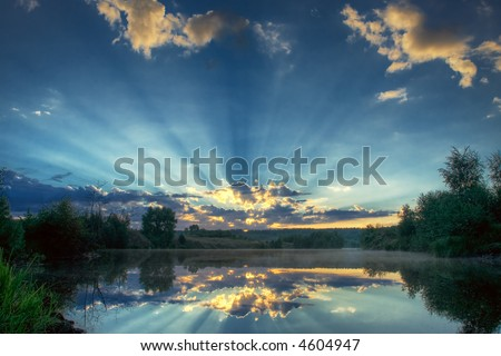 The sun makes the way through clouds - stock photo