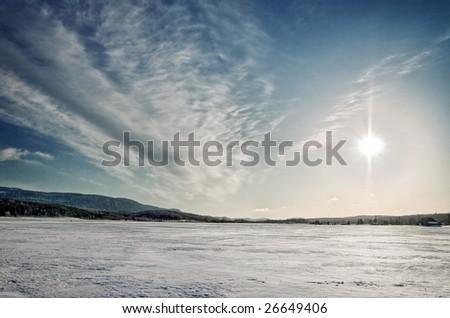 The sun over a field in a  winter landscape - stock photo