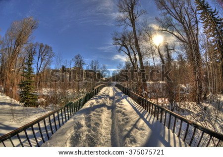 The sun over a snowy bridge road with a mountain landscape in Aspen during the winter. - stock photo