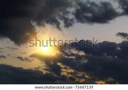 The sun peeps out from behind the dark clouds. A very symbolic photo. - stock photo