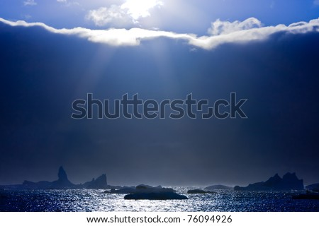 The sun peeps out from the edge of the clouds. On the horizon are visible icebergs - stock photo