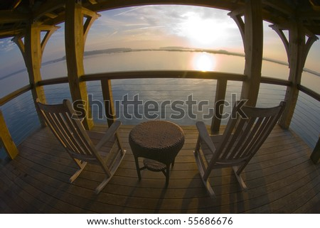 The sun rises on a tranquil ocean with a table and chairs in the foreground - stock photo