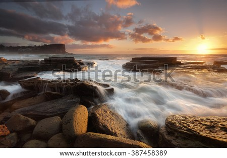 The sun rises on 2016.  New Years Day at Avalon Beach with views north and foreground tidal flows over rocks - stock photo