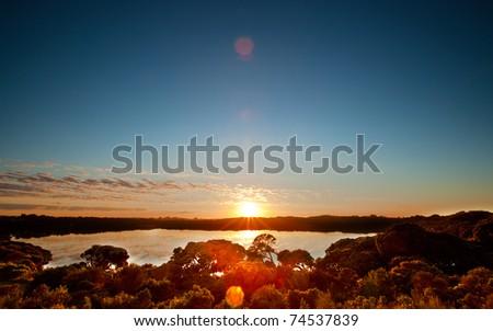 The sun rises over a peaceful lake in South Australia - stock photo