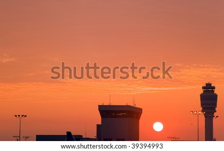 The sun rises over an airport terminal and control tower - stock photo
