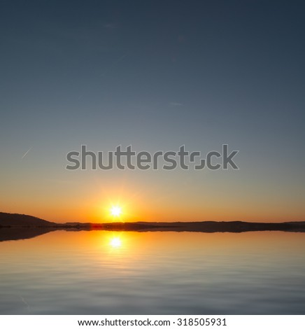 The sun rises over calm Mediterranean waters - stock photo