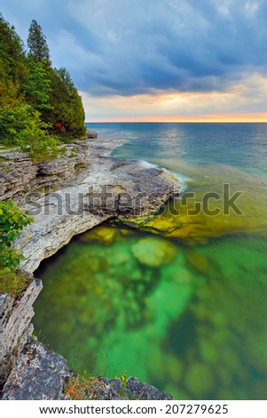 The sun rises over the beautiful and rocky Cave Point on the Lake Michigan coast of Door County, Wisconsin. - stock photo