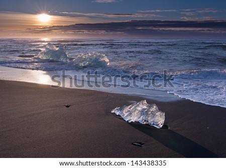 The sun rises over the ice beach in Iceland. - stock photo