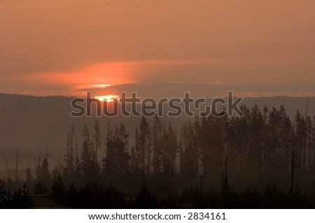 The sun rises over the mountains in Yellowstone National Park