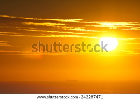 The sun rises over the ocean as a ship sails past on the horizon. - stock photo