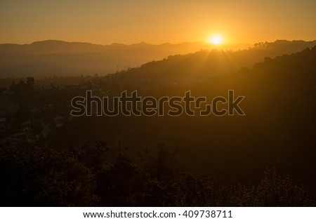 The sun rises over the San Fernando Valley shooting beams of light through the foggy landscape in Los Angeles, CA - stock photo