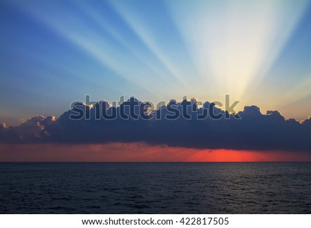 The sun rises over the sea and hides behind a cloud, and only the sun's rays light up the sky - stock photo