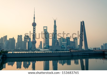 The sun rises over the skyscrapers of Shanghai. - stock photo