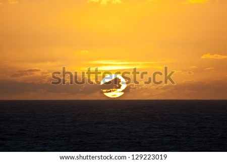The sun rises over the tropical South Pacific Ocean in French Polynesia. - stock photo