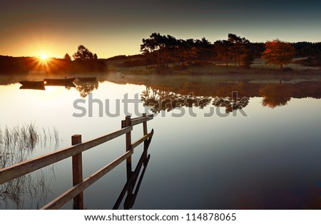 The Sun rising over a calm Knapps Loch, with a wooden fence leading in to the water and tree reflections in the distance. Scotland - stock photo