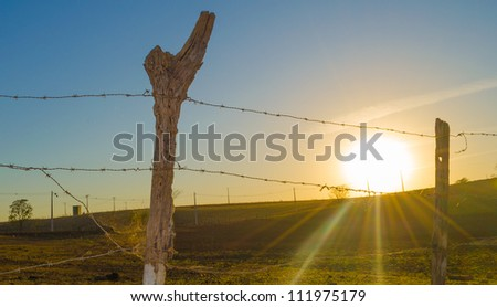 The sun rising with a wood and barbed wire fence in the foreground - stock photo