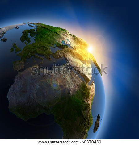 The sun's rays from the rising sun illuminate the earth in outer space - stock photo
