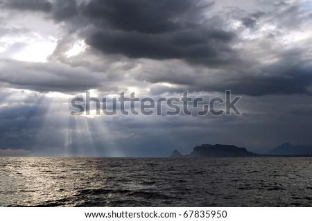 The sun's rays passing through the storm clouds over the sea - stock photo