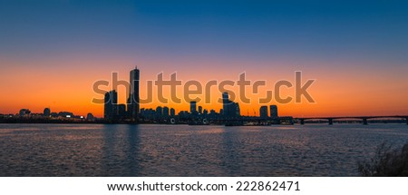 The sun sets behind the skyscrapers of Seoul, South Korea. - stock photo