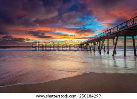 The sun sets on a beach at a pier.