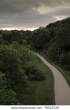 The sun sets on a cloudy evening over Jesmond Dene in Newcastle upon Tyne, England. Photograph taken from the Armstrong Bridge. - stock photo