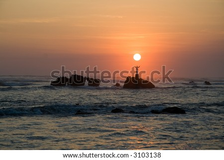The sun sets over a statue of Jesus out in the ocean in El Salvador - stock photo