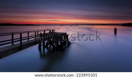 The Sun sets over Poole Harbor in Dorset. Hamworthy pier jetty - stock photo