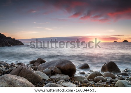 The sun sets over Porth Nanven Cove near Penzance in Cornwall, also known as Cot Valley - stock photo