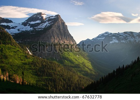 The sun sets over the mountains along Going to the Sun Road in Glacier National Park, Montana. - stock photo