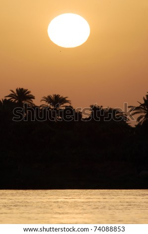 The sun sets over the Nile river in Egypt