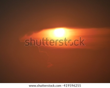 The sun sets over the ocean during this long exposure. - stock photo