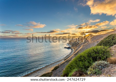 The sun sets over the Point Vicente lighthouse at Pelican Cove in California. - stock photo