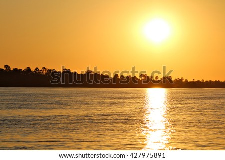 The sun sets over the Zambezi River, the border between Zimbabwe and Zambia, Africa. - stock photo
