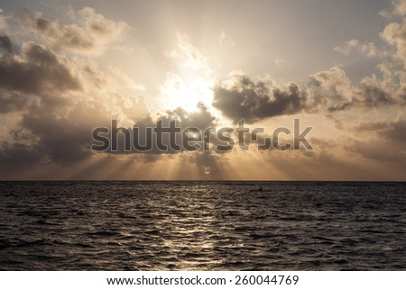 The sun sets rises off the coast of Belize in the Caribbean Sea. This tropical area is known for its beautiful scuba diving, snorkeling, and excellent fishing. - stock photo