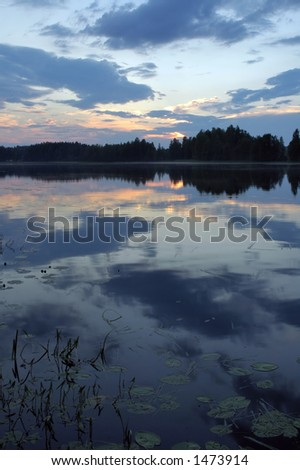 the sun setting behind trees and making a reflection on the lake - stock photo