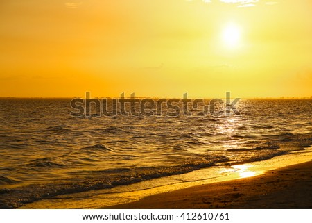 The sun setting on a bright orange sky above the Gulf of Mexico in Fort Myers Beach with the beach in the foreground. - stock photo