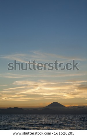 The sun setting over a hill and lake. - stock photo