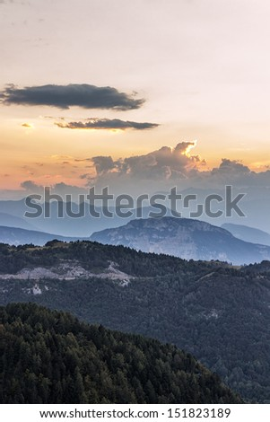 The sun setting over the mountains in Italy - stock photo
