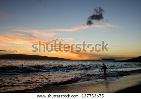 The sun setting over the ocean at Big Beach on the Island of Maui. The island Kahoolawe is in the background. - stock photo
