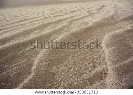 The sun shimmers off of the rippled surface of an expanse of san dunes - stock photo