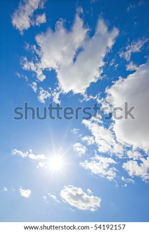 The sun shining brightly mid day in a blue sky with white fluffy clouds. Vertical image. - stock photo
