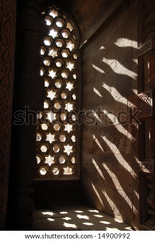 The sun shining through the ornately carved stone window inside the Alai Darwaza, built in 1311 as the southern entrance to the Qutab Minar, one of the largest standing stone minarets in the world. - stock photo