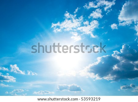 The sun sparkling behind clouds - stock photo