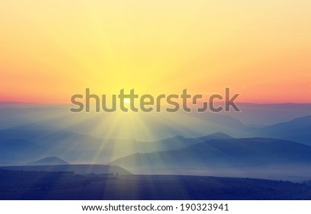 The sun with rays rises over the mountains. Vintage picture