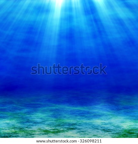 The sunbeams penetrate the depths of the ocean. Sea and sandy bottom at sunny day.  - stock photo