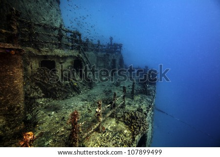 The sunken shipwreck Eagle in the Florida Keys. A ship laying in the sand on it's side with the wreck broken in half. Blue water surrounding coral covered boat. with a lot of fish and animals. - stock photo