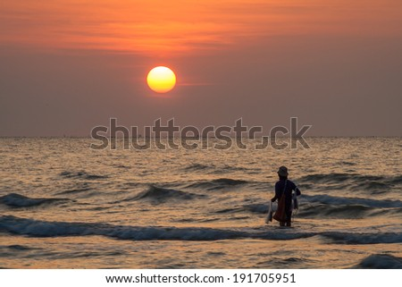 The sunrise and silhouette image of fisherman in sea
