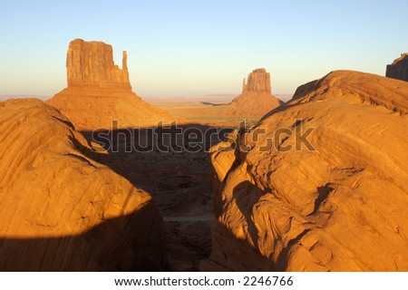 The sunset in Monument Valley (Navajo Nation, Utah). Two mittens are framed by two boulders... - stock photo